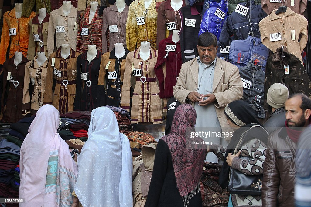 Women browse clothing at a market in Rawalpindi, Pakistan, on Sunday, Dec. 30, 2012. Pakistan's economy will probably expand 3.5 percent in the 12 months through June, the International Monetary Fund forecast Nov. 29, less than the 4.3 percent predicted by the government. Photographer: Asad Zaidi/Bloomberg via Getty Images