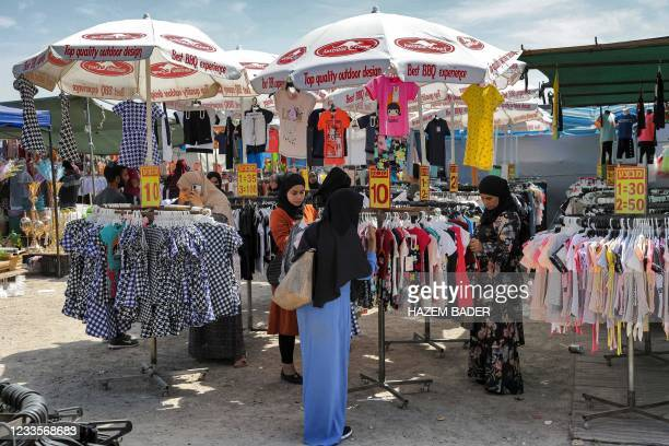 Women browse dresses as they shop for clothing at a market in the Bedouin town of Rahat in Israel's southern Negev region on June 8, 2021. - The...