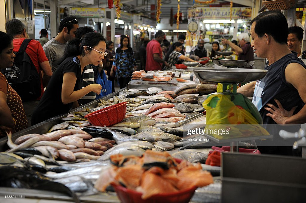 Women browse fish at a market in the area of Little India in Singapore, on Saturday, Dec. 29, 2012. Singapore may grapple with elevated inflationary pressures for a third year in 2013, reducing scope for the central bank to provide stimulus to an economy that probably entered a technical recession this quarter. Photographer: Munshi Ahmed/Bloomberg via Getty Images