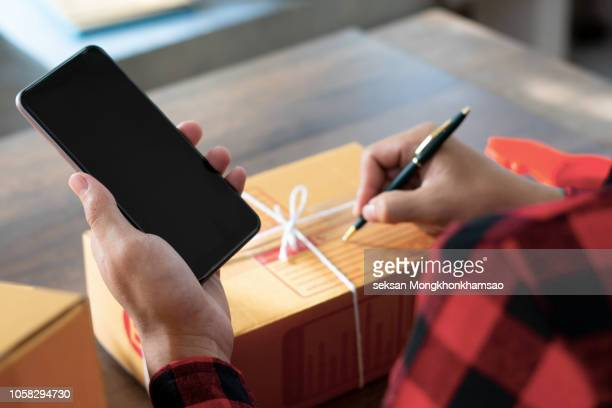 Women business owner using phone for confirm address of customer and writing in packing box at home office. online shopping SME entrepreneur or freelance working concept.