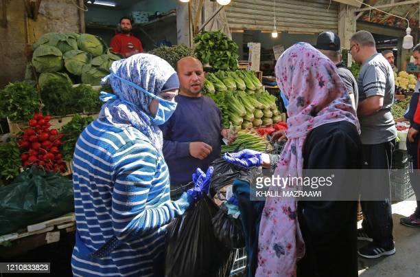 Women buy fresh vegetables at a market ahead of the Muslim holy month of Ramadan, during the novel coronavirus pandemic crisis in the Jordanian...