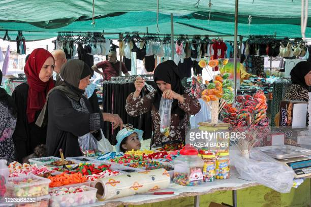 Women buy sweets at an open-air market in the Bedouin town of Rahat in Israel's southern Negev region on June 8, 2021. - The Bedouin belong to the...