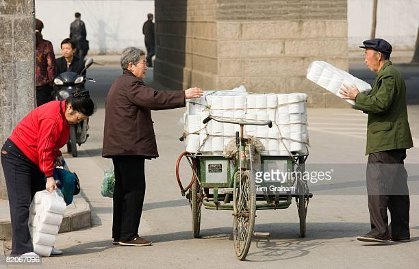 Women buy toilet paper from tradesman from carts in street market by the City Wall Xian China