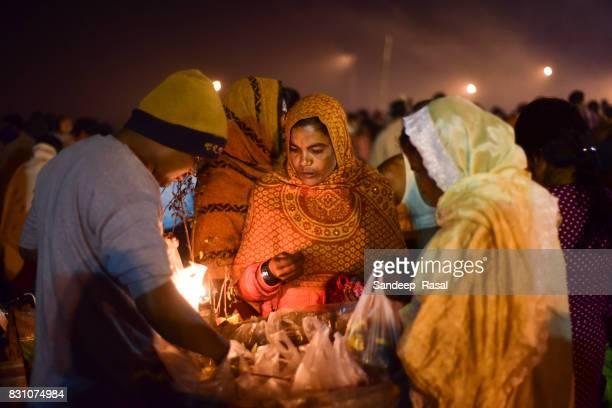 a women buying flowers during ganga sagar fair. - ganga sagar stock photos and pictures