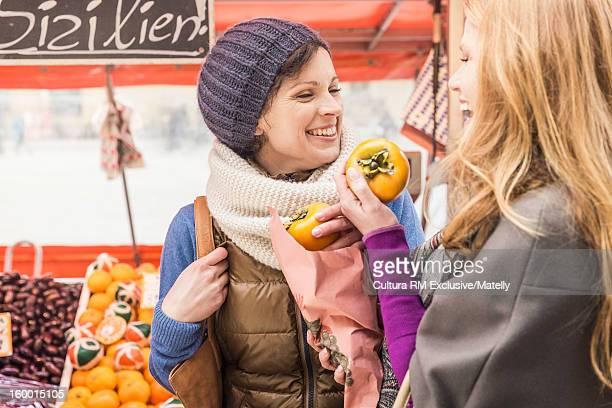 Women buying fruit in market