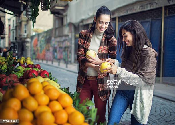 women buying fruits from the street vendor - bazaar stockfoto's en -beelden