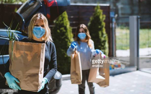 women buying groceries and back home. wearing protective mask and gloves - volunteer stock pictures, royalty-free photos & images