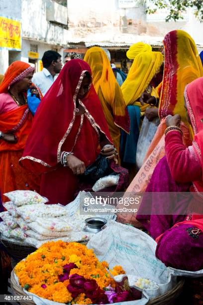 Women buying prasada from a market stall Pushkar Ajmer Rajasthan India