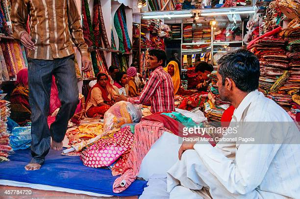Women buying saris in a textile shop in trhe blue old city