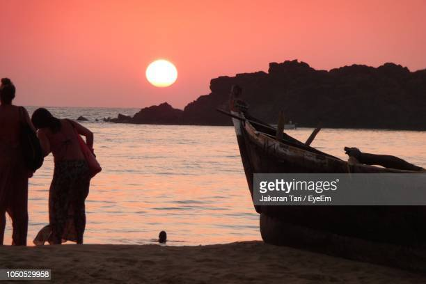 women by boat at beach against sky - tari stock pictures, royalty-free photos & images