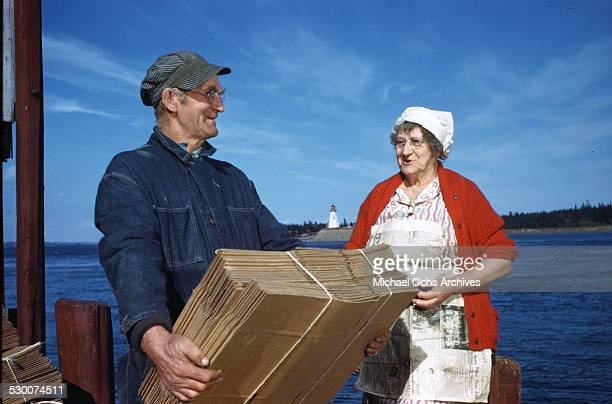 A women cannery worker talks to a local fishermen in Lubec Maine