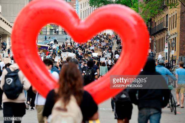 A women carries a heart shaped ballon as people march through the city during a Black Lives Matter rally in response to the death of George Floyd and...
