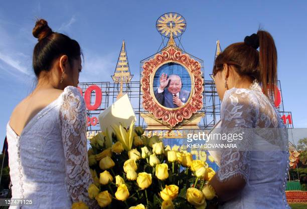 Women carry a bouquet of flowers for Cambodia's former king Norodom Sihanouk during a ceremony at the Royal Palace in Phnom Penh on October 30 2011...