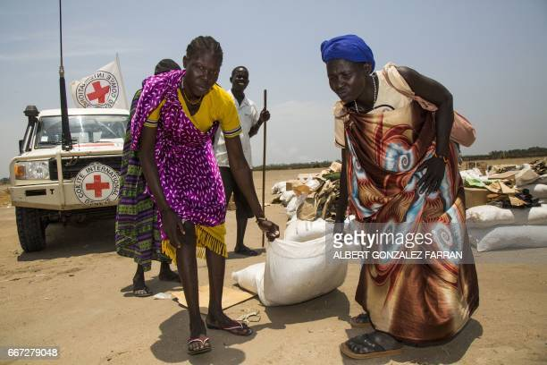 Women carry a sack of seeds distributed by the International Committee of the Red Cross in the opposition controlled town of Thonyor in Leer county...