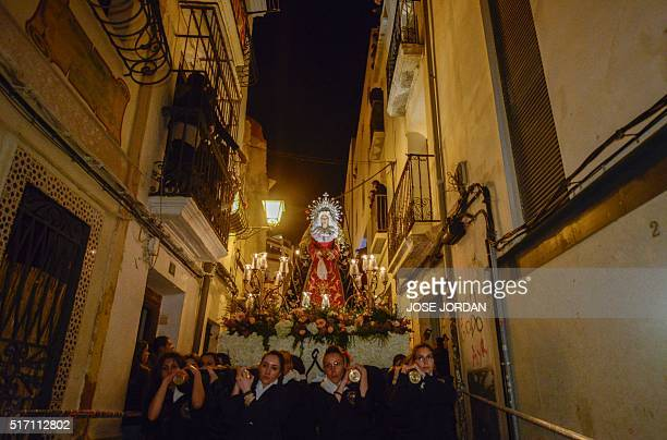 Women carry an effigy of Jesus Christ on the cross down steps during the Cristo de la Fe populary known as the gypsy Christ parade during a Holy Week...