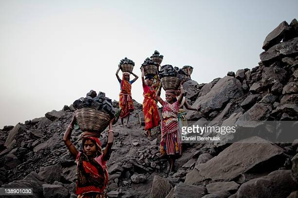 Women carry baskets of coal back to their village for sale after having scavenged the coal illegally from an opencast coal mine in the village of...