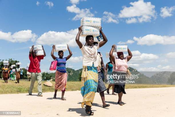 TOPSHOT Women carry boxes load of porridge for their children on March 13 in the Mutoko rural area of Zimbabwe Eastern Zimbabwe receives help to...