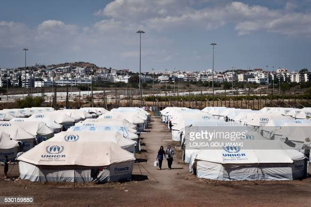 Women carry bucket with laundry between UNHCR tents set in the former Helliniko Olympic complex used as refugee camp for mainly Afghani refugees on...