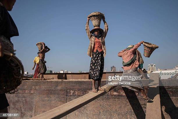Women carry buckets of gravel on the banks of the Irrawaddy River next to the oil recycling company on December 16 2013 in Yangon Myanmar Gravel...