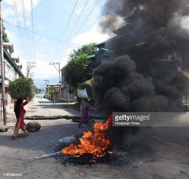 Women carry bundles of grass past a burning tyre near a barricade set by local protesters to block the road during a protest against the abolishing...
