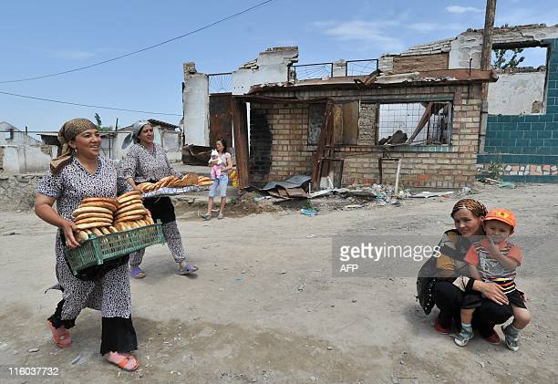 Women carry cakes in the village of Shark near the town of Osh some 750 km from Bishkek on June 11 2011 Kyrgyzstan marked one year since ethnic...
