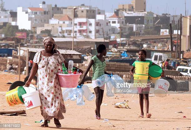 Women carry empty containers to fill with water in a neighbourhood of Dakar on September 23 2013 following a water shortage A number of...