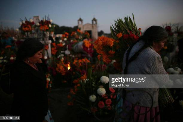 Women carry flowers as they arrive at the local cementery during the Day of the Dead celebration known in spanish as Dia de los Muertos on November...