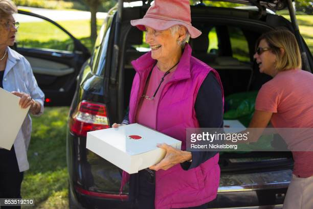 Women carry freshly baked apple pies to a table for a benefit sale at the Congregational Church in Charlotte Vermont September 22 2017