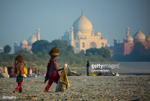 Women carry manure near the famous indian sightseeing point Taj Mahal on December 01 2012 in Agra Uttar Pradesh India The UNESCO World Heritage and...