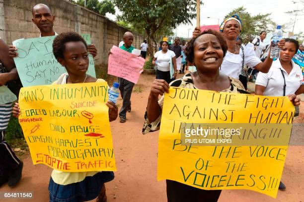 Women carry placards as rights activists under the umbrella of the Justice Development and Peace commission march against the illegal human...