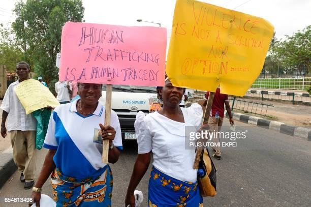 Women carry placards as rights activists under the umbrella of the Justice Development and Peace commission a protest march against violence...