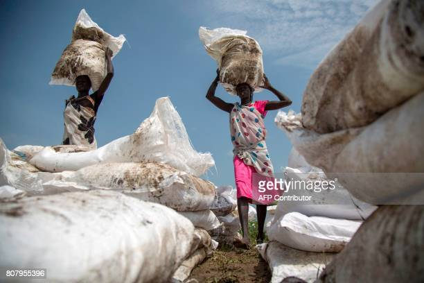 Women carry sacks of food airdropped by the World Food Programme and distributed by the NGO Oxfam in Padding near Lankien Jonglei South Sudan on July...
