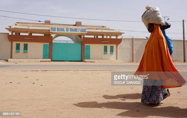 Women carry sacks on their heads as they walk past the Sidi Mohamed stadium in Agadez northern Niger on April 6 2017 Agadez the gateway to the desert...