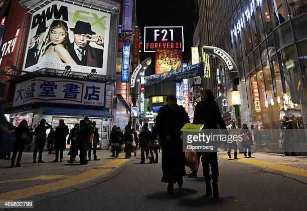 Women carry shopping bags while walking through the Shibuya district of Tokyo, Japan, on Sunday, Feb. 16, 2014. Japans economy grew at a pace slower...