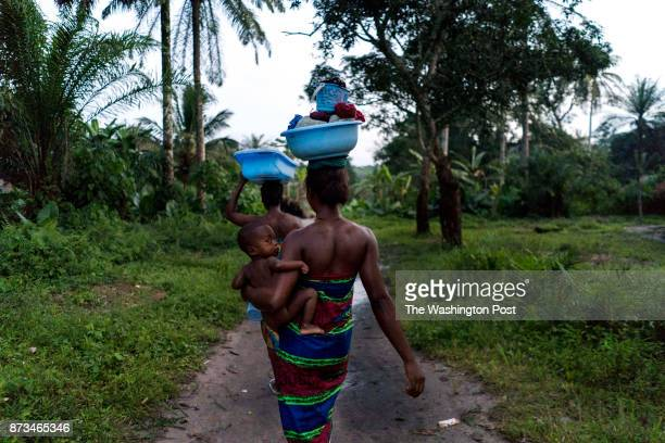 CONGO Women carry washing back to their thatched huts in a remote northern village within Central Africa named Manfuette where a team from the Center...