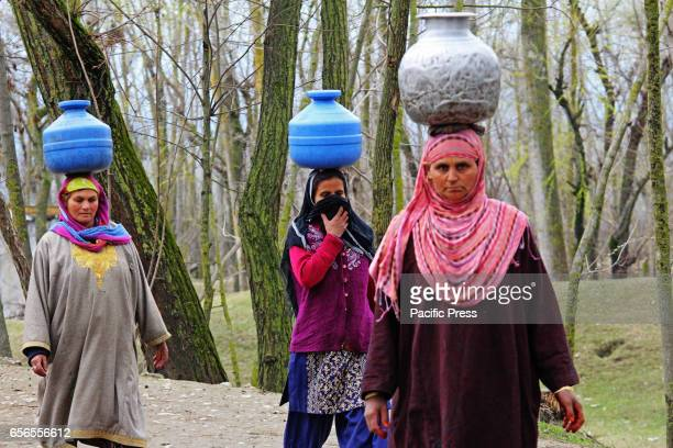 Women carry water containers because of unavailability of the portable water through taps in Baramulla district