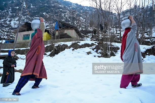 Women carry water pitchers on their head after a water pipe got frozen due to sub zero temperatures on the outskirts of Srinagar on January 3 2020