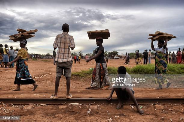 Women carry wood in the outskirts of Lilongwe on March 11 2016 / AFP / ARIS MESSINIS / RESTRICTED TO EDITORIAL USE