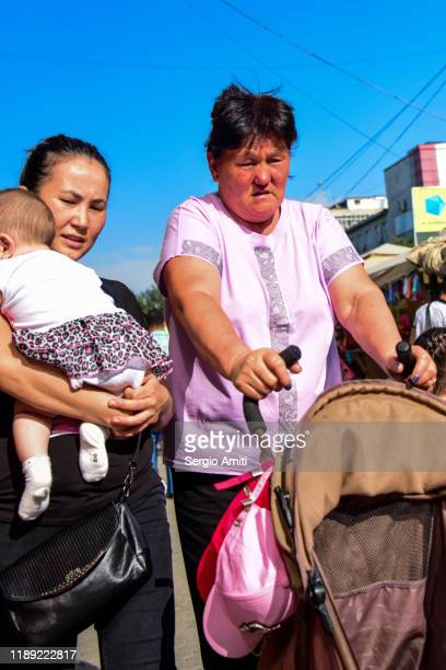 women carrying a baby and pushing a pushchair - sergio amiti stock pictures, royalty-free photos & images