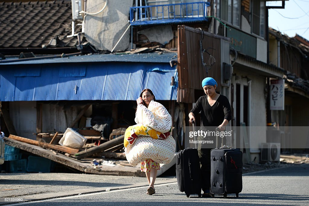 A women carrying a comforter and a man carrying suitcases are seen in front of a collapsed house a day after the 2016 Kumamoto Earthquake on April 15, 2016 in Mashiki, Kumamoto, Japan. As of April 15 morning, at least nine people died in the powerful earthquake with a preliminary magnitude of 6.4 that struck Kumamoto Prefecture on April 14, 2016.