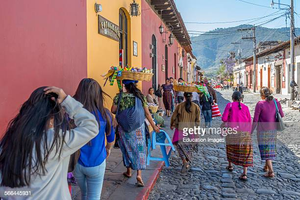 Women carrying baskets on their head while walking down the street in Antigua Guatemala