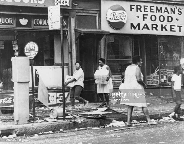 Women carrying boxes along the debris-strewn sidewalk, passing Freeman's Food Market, as looting continued during the riots in Newark, New Jersey,...