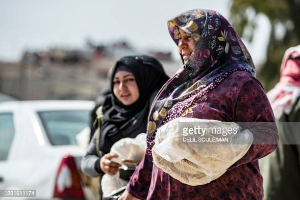 Women carrying bread walk through a commercial district in Syria's northeastern city of Qamishli on March 9, 2021. - Syria's decade-long war has seen...