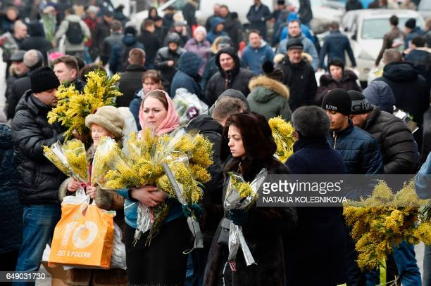 Women carrying bunches of mimosa walk next to a flower market in Moscow on March 7 2017 on the eve of International Women's Day / AFP PHOTO / Natalia...