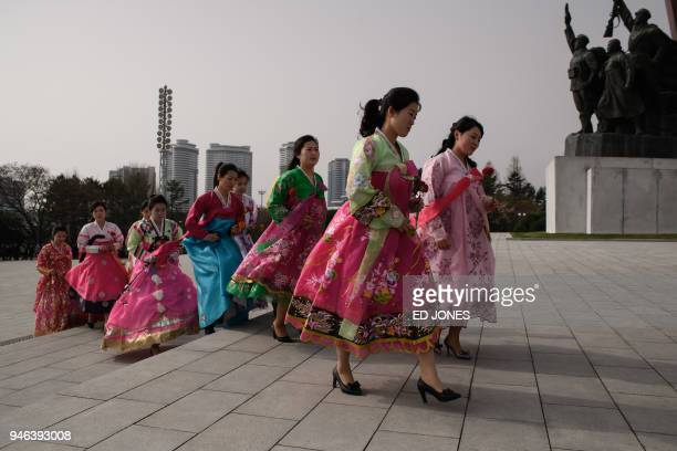 TOPSHOT Women carrying flowers arrive at Mansu hill to pay their respects before the statues of late North Korean leaders Kim Il Sung and Kim Jong Il...