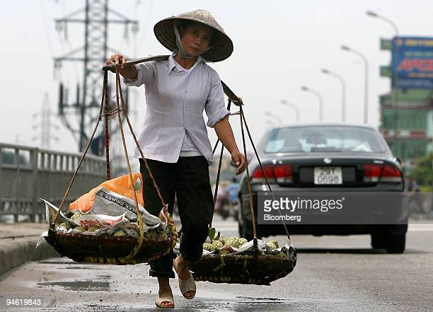 A women carrying fruit walks along a main highway in Hanoi Vietnam on Sunday August 20 2006