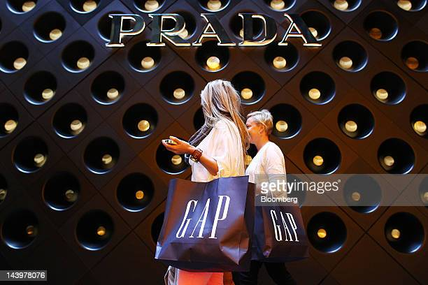 Women carrying Gap Inc shopping bags walk past a Prada SpA store in Sydney Australia on Saturday May 5 2012 The Australian government intends to...