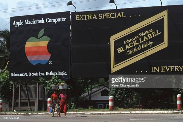 BURMA YANGON RANGOON MYANMAR Women carrying loads on their heads walk past two big black billboards advertising Johnnie Walker Black Label Whisky and...