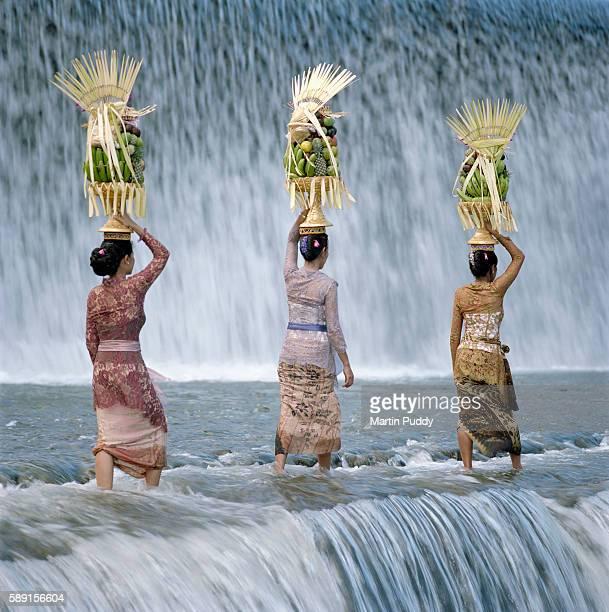 Women carrying offerings walking across waterfall