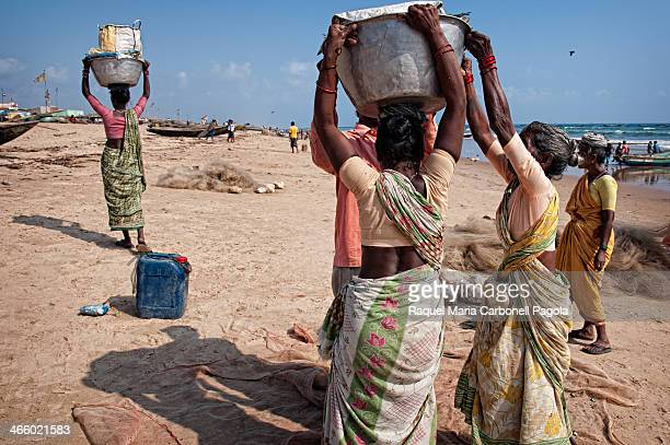 Women carrying pots of fish for selling